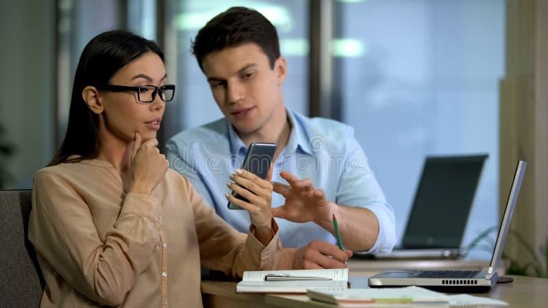 Desenhistas profissionais que discutem o n?cleo e processador do smartphone novo, dispositivos imagem de stock