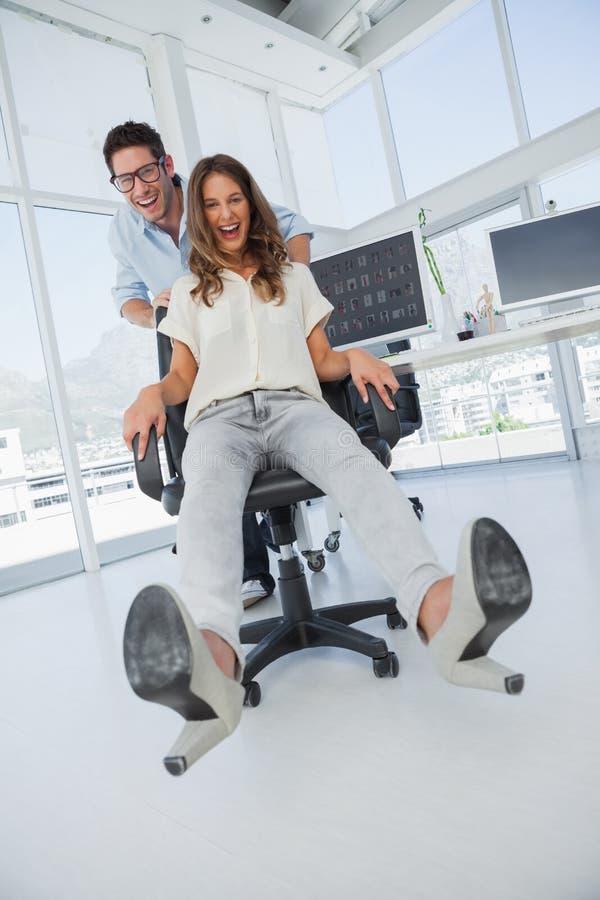 Desenhistas que têm o divertimento com sobre uma cadeira de giro imagem de stock