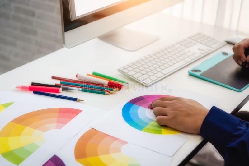 Desenhistas que trabalham com as amostras da amostra de folha da cor para a Web do projeto no local de trabalho no escritório con fotografia de stock