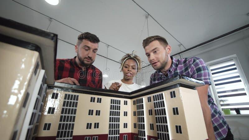 Desenhistas que trabalham com o modelo da casa fotografia de stock royalty free