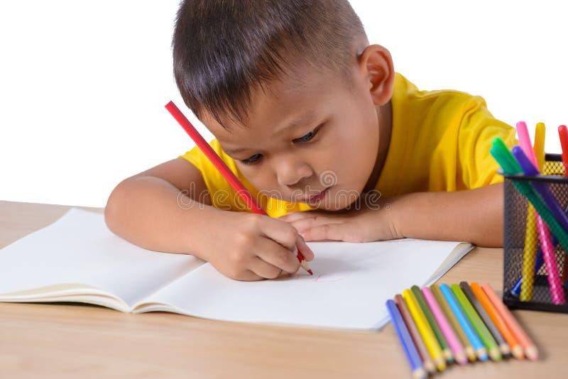 Desenho alegre bonito da criança usando o lápis da cor ao sentar-se na tabela no fundo branco fotografia de stock