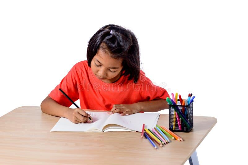 Desenho alegre bonito da crian?a usando o l?pis da cor ao sentar-se na tabela isolada no fundo branco imagens de stock