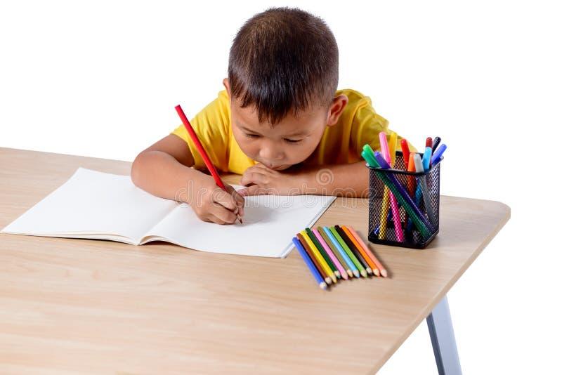 Desenho alegre bonito da crian?a usando o l?pis da cor ao sentar-se na tabela isolada no fundo branco foto de stock royalty free