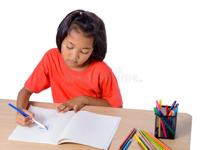 Desenho alegre bonito da crian?a usando o l?pis da cor ao sentar-se na tabela isolada no fundo branco fotos de stock royalty free