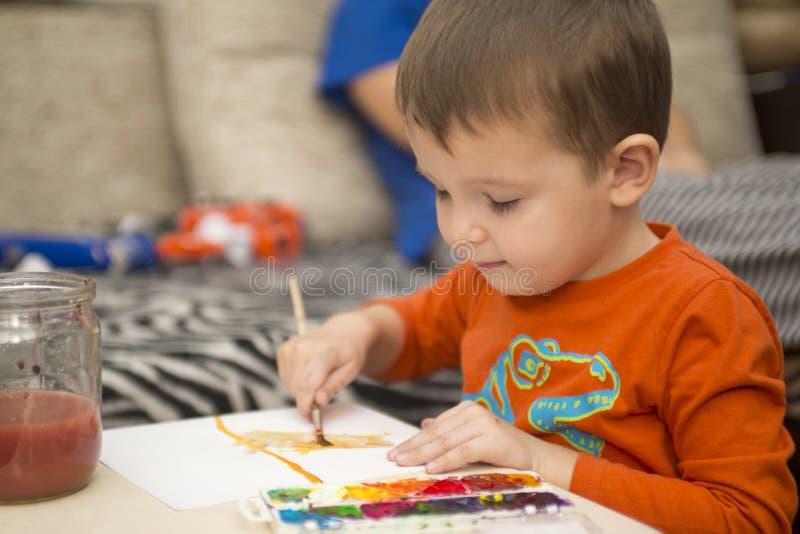 Desenho alegre feliz da criança com escova usando ferramentas de uma pintura Conceito da faculdade criadora imagens de stock royalty free