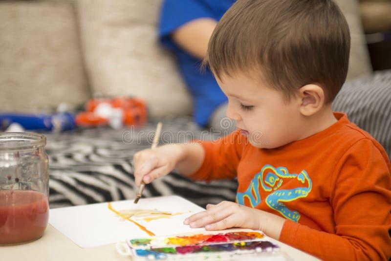 Desenho alegre feliz da criança com escova usando ferramentas de uma pintura Conceito da faculdade criadora fotografia de stock