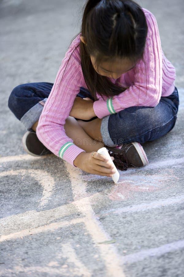 Desenho asiático da menina na terra com giz do passeio imagens de stock