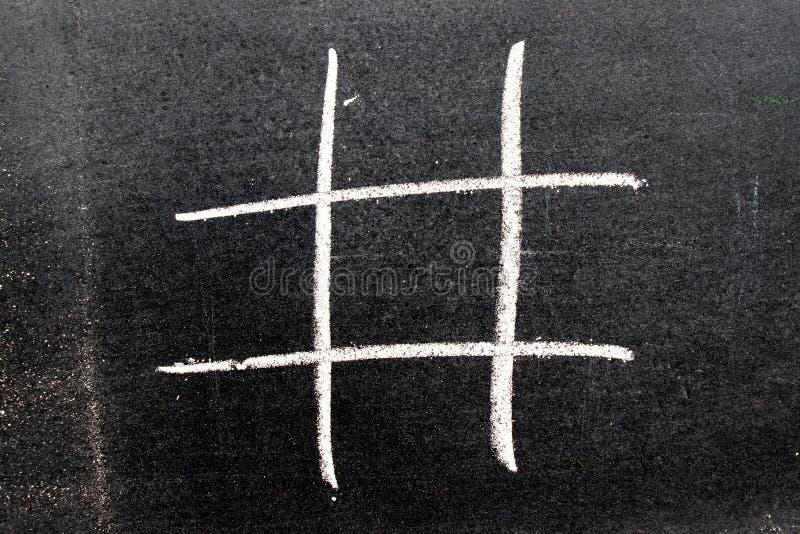Desenho branco da mão do giz da cor como a forma do hashtag no quadro-negro foto de stock royalty free