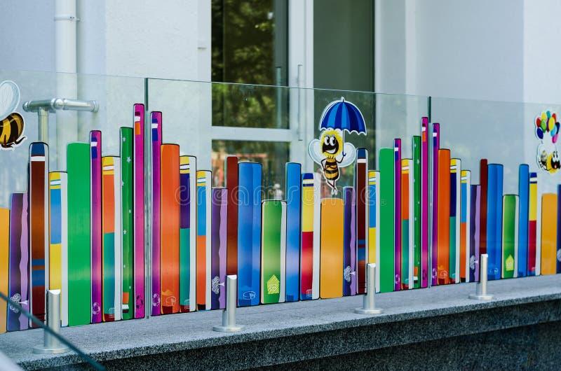 Desenho colorido brilhante em uma cerca de vidro na entrada à biblioteca de crianças da cidade fotografia de stock