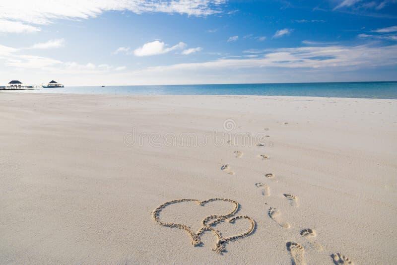 Desenho da forma do coração na areia no fundo tropical da praia, o romântico e da lua de mel do conceito para pares imagens de stock