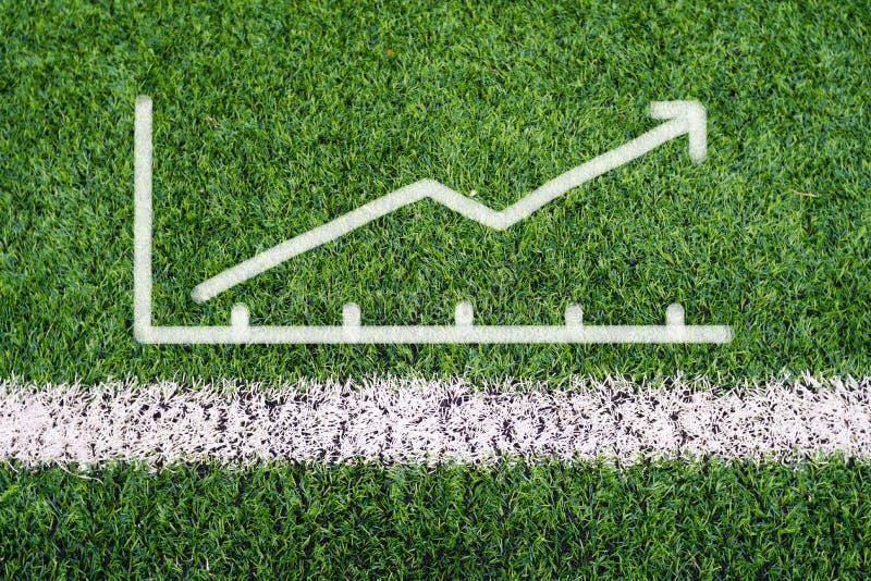 Desenho da mão do gráfico de negócio na grama do campo de futebol fotografia de stock royalty free