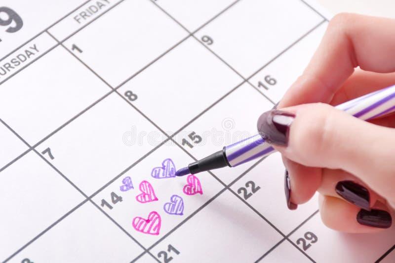 Desenho da mão da menina e forma colorindo do coração no calendário para o dia de Valentim com pena de feltro foto de stock royalty free