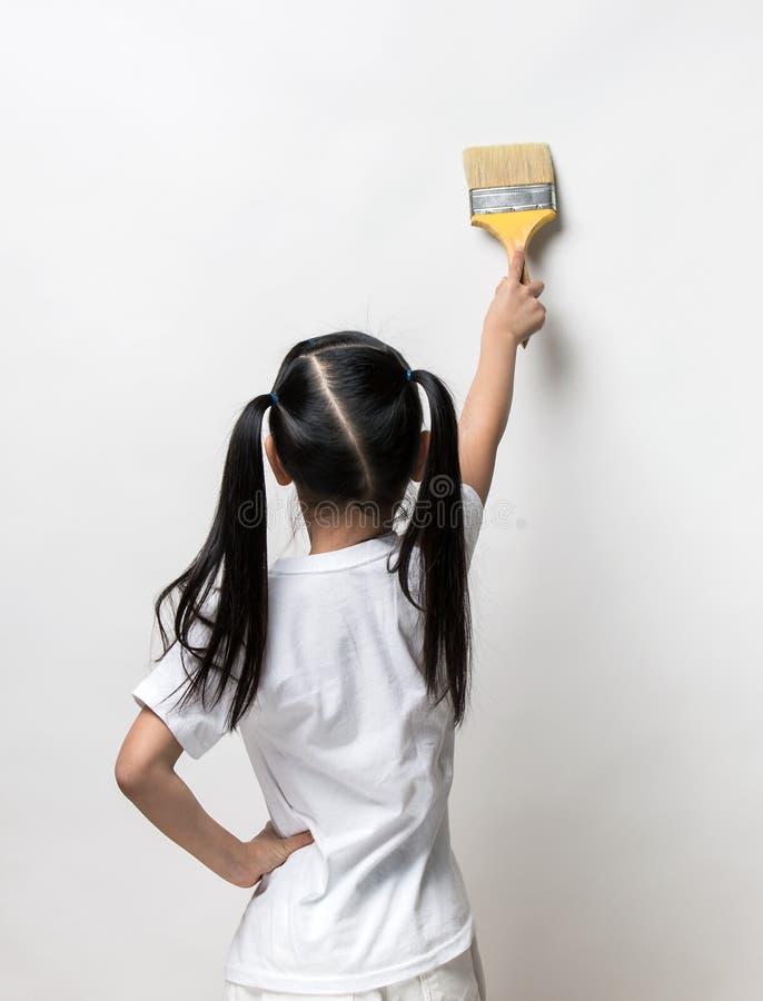 Desenho da menina algo que usa a escova de pintura fotografia de stock
