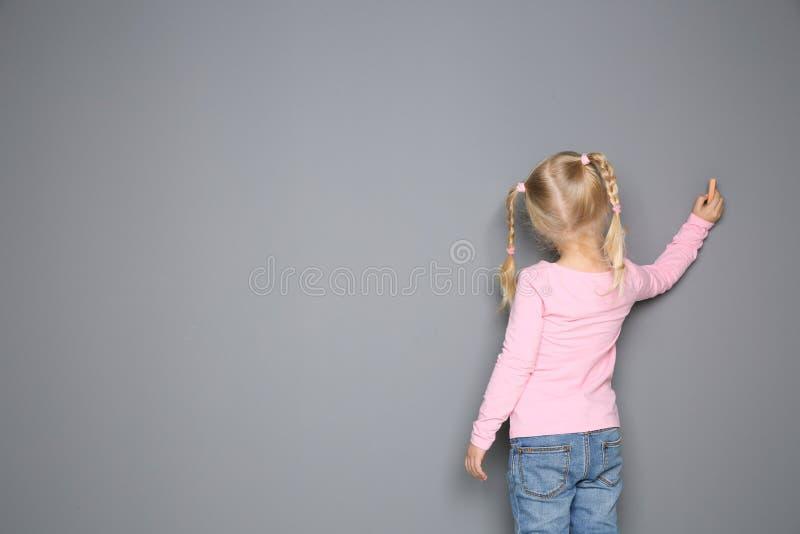 Desenho da menina com giz colorido no fundo cinzento fotos de stock