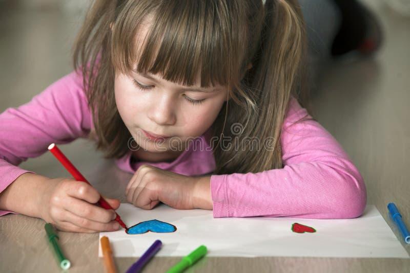 Desenho da menina da crian?a com cora??o colorido dos past?is dos l?pis no Livro Branco Educa??o da arte, conceito da faculdade c foto de stock royalty free