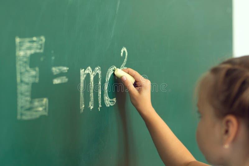 Desenho da menina na fórmula e=mc2 do quadro Educação e conceito da escola fotos de stock royalty free
