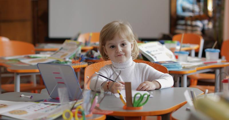 Desenho da menina na tabela na sala de aula Educa??o Crian?a que senta-se em uma mesa fotografia de stock royalty free