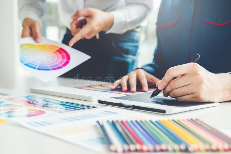 Desenho da reunião do designer gráfico na tabuleta de gráficos no local de trabalho imagens de stock royalty free