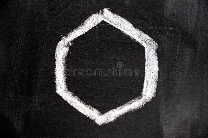 desenho de giz branco na forma vazia do hexágono no quadro-negro imagens de stock
