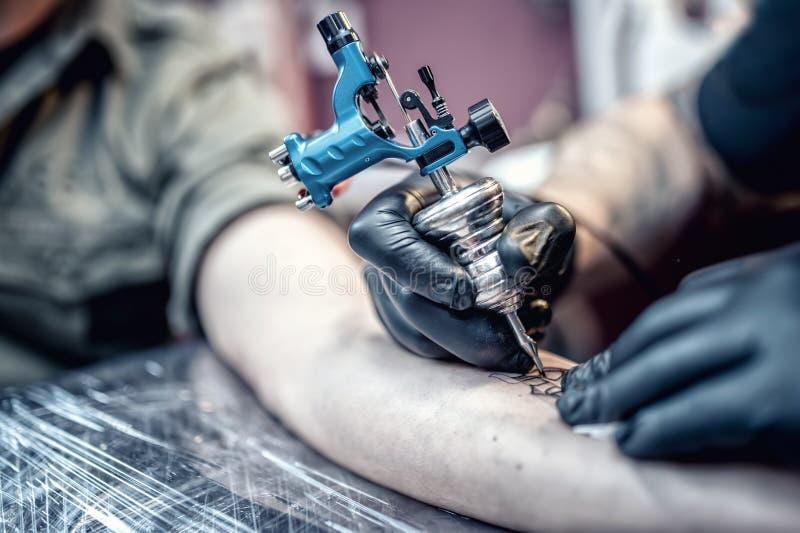 Desenho do artista da tatuagem no cliente com ferramentas especiais fotos de stock