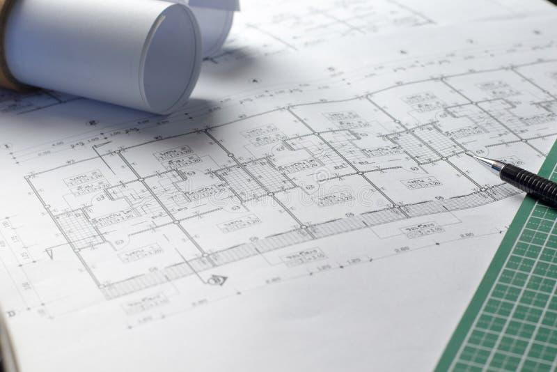 Desenho do projeto dos planos arquitetónicos com rolos dos modelos imagem de stock