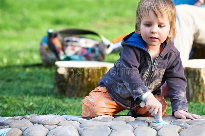 Desenho do rapaz pequeno com giz do passeio no parque imagens de stock royalty free