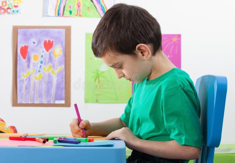 Desenho do rapaz pequeno na lição da arte foto de stock