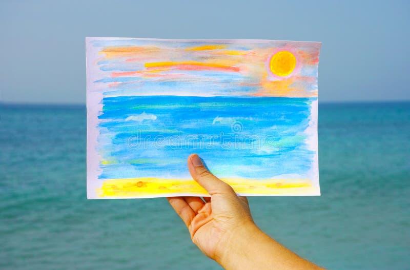 Desenho do Watercolour na mão da mulher contra o mar e o céu foto de stock royalty free