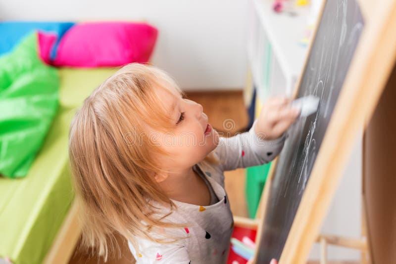 Desenho feliz da menina na placa de giz em casa imagem de stock