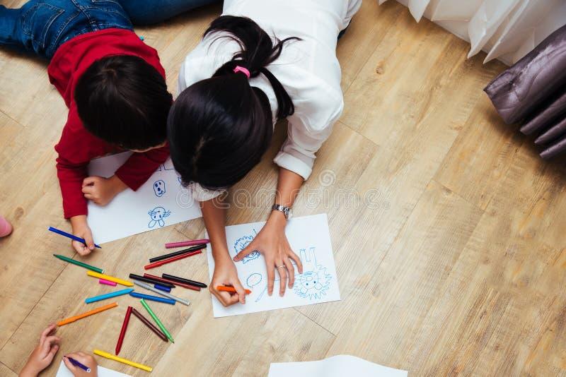Desenho feliz da pintura do jardim de infância do menino e da menina da criança do grupo das crianças da família da vista superio fotos de stock