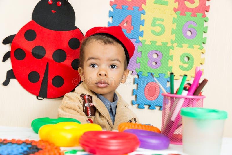 Desenho preto afro-americano do menino com os lápis coloridos no pré-escolar no jardim de infância foto de stock