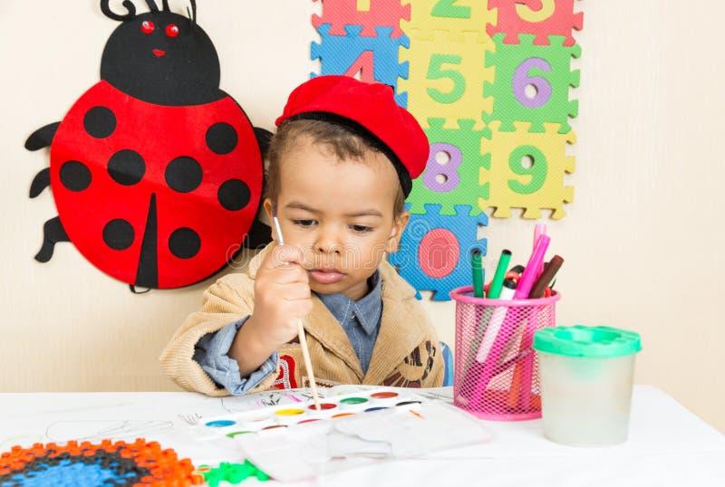 Desenho preto afro-americano do menino com os lápis coloridos no pré-escolar no jardim de infância foto de stock royalty free