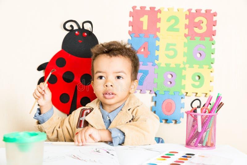 Desenho preto afro-americano do menino no pré-escolar na tabela no jardim de infância fotos de stock