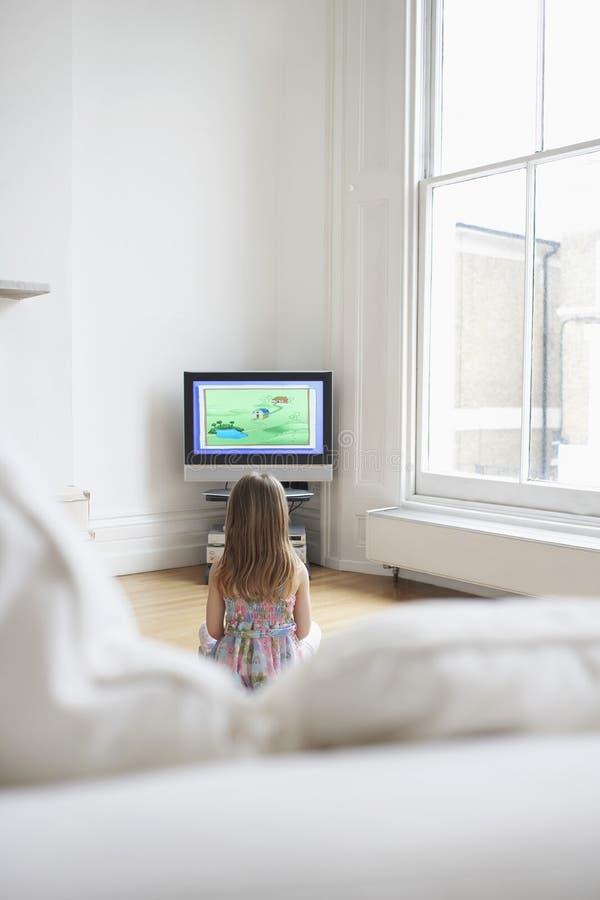 Desenhos animados de observação da menina na tevê em casa ilustração stock