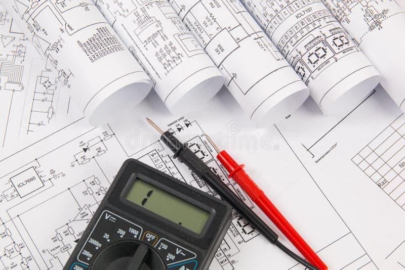 Desenhos de engenharia elétrica e multímetro digital foto de stock royalty free