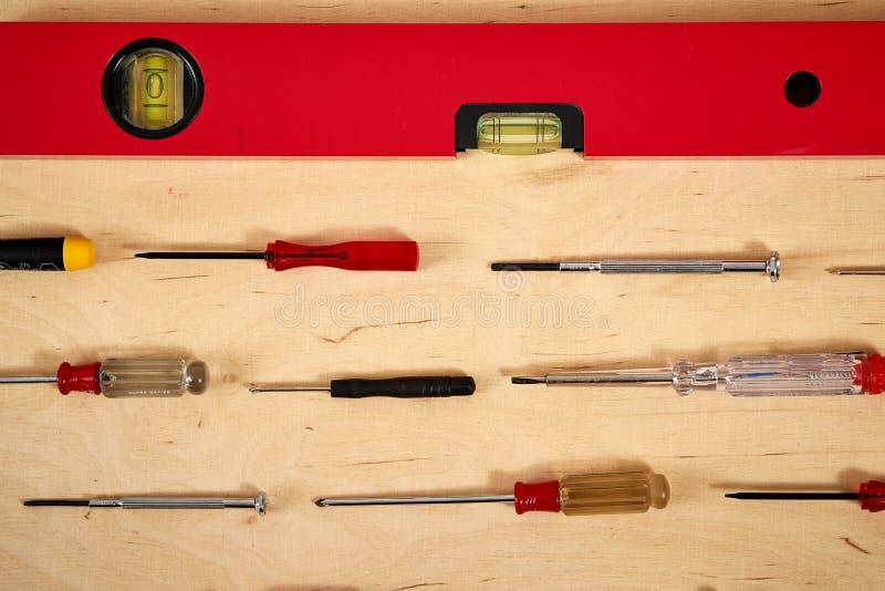 Deseniowy tło różnorodni śrubokręty z spirytusowym poziomem na drewnianym praca stole zdjęcia royalty free