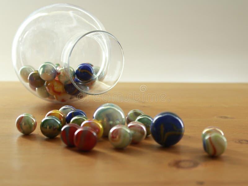 Desenrolar colorido dos mármores de um frasco de vidro em um tampo da mesa fotos de stock
