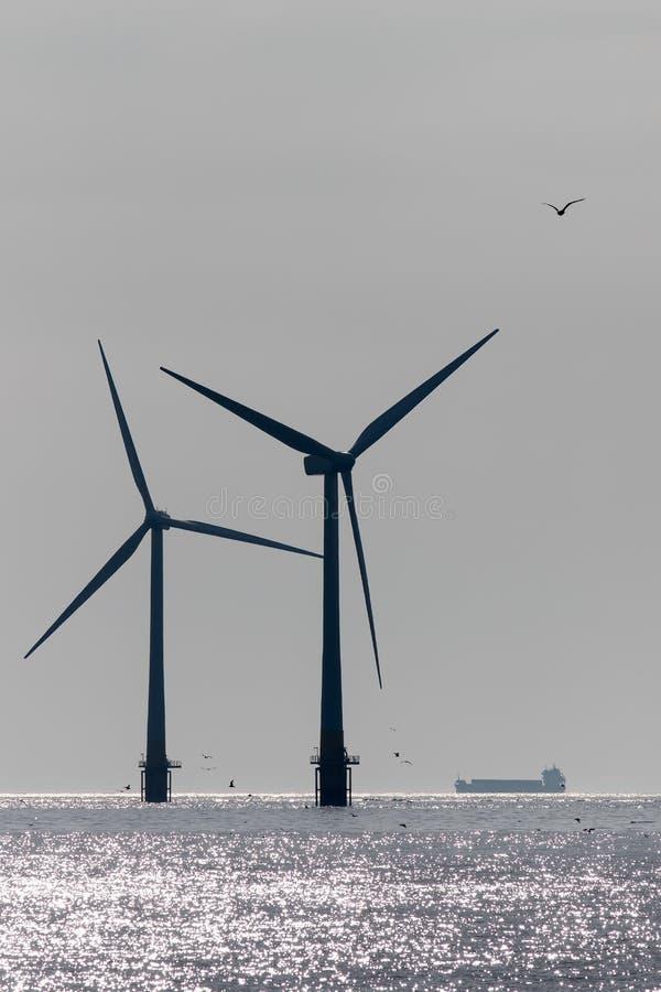 Desenvolvimento limpo da produção energética Silhueta a pouca distância do mar da turbina das energias eólicas com embarcação da  imagens de stock royalty free