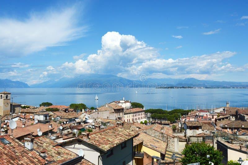 从Desenzano城堡的惊人的全景在有老城市屋顶、山、白色云彩和风船的加尔达湖在湖, Desen 库存照片