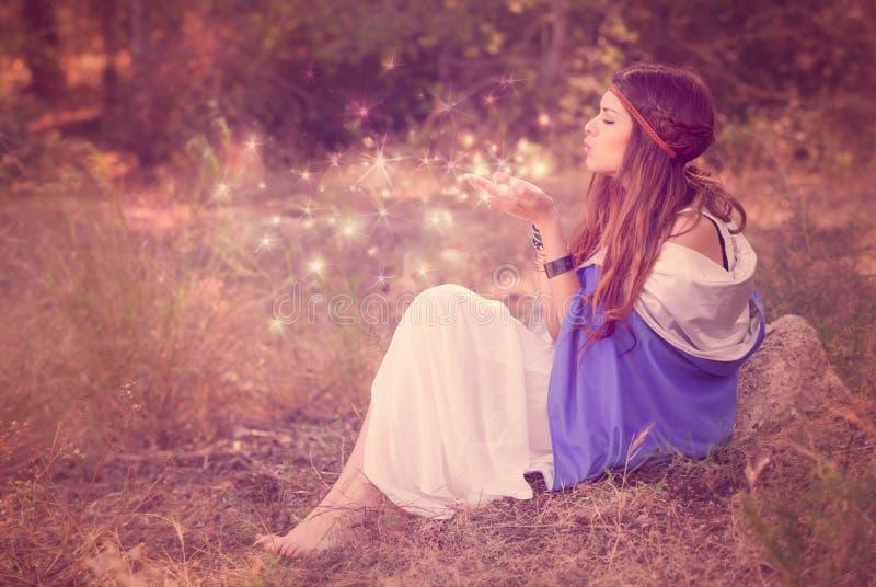 Deseos que soplan de la mujer en hada o duende del bosque imagenes de archivo