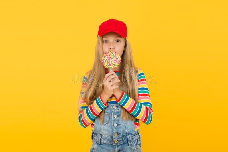 Deser Yummy Małe dziecko liże słodycze na żółtym tle Dziewczyna woli słodki deser od zdrowego jedzenia obrazy royalty free