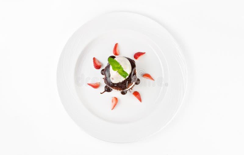 Deser z czekoladowym gąbka tortem, waniliową śmietanką, wiśnią, lody i truskawkami na talerzu na białym tle, fotografia royalty free