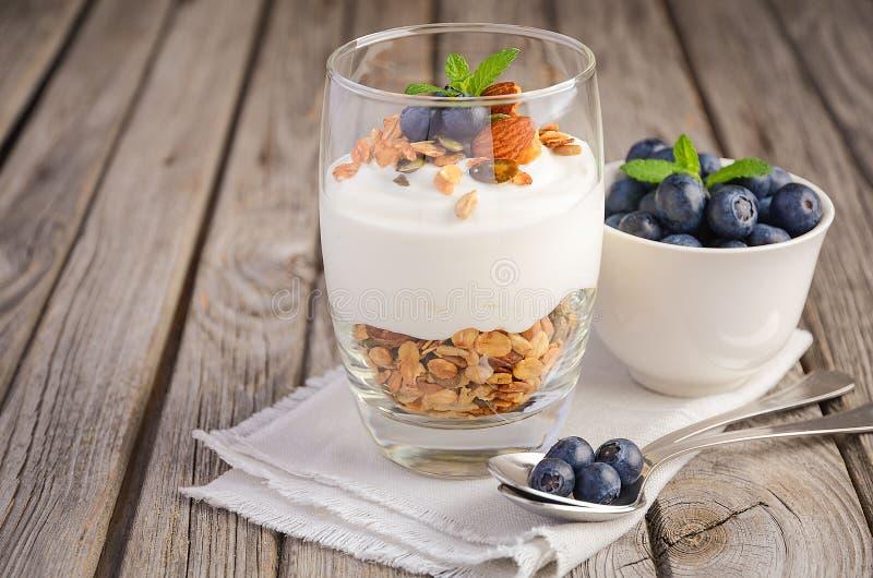 Deser z domowej roboty granola, jogurtem i czarnymi jagodami na nieociosanym tle, zdjęcie stock