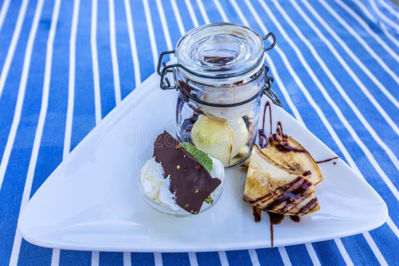 Deser z lody i bananami z czekoladą w szklanym słoju zdjęcia stock