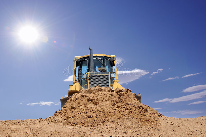 Desert bulldozer. A bulldozer moving mud on a hot day at a construction site in a desert with sun shining brightly royalty free stock images