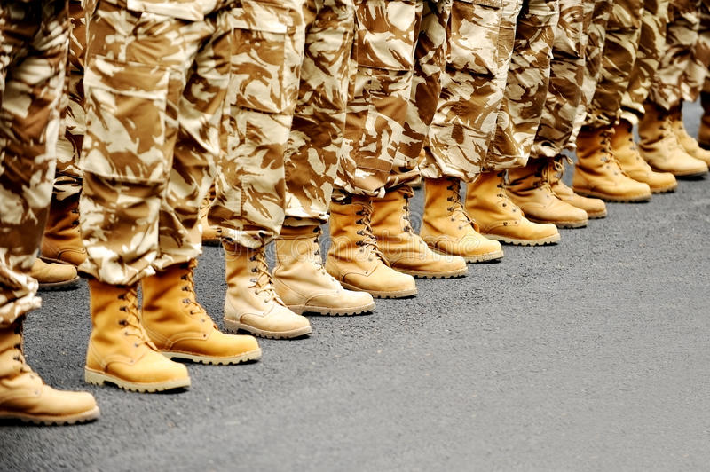 Desert camouflage uniform. Soldiers feet in desert camouflage military uniform in rest position royalty free stock photo