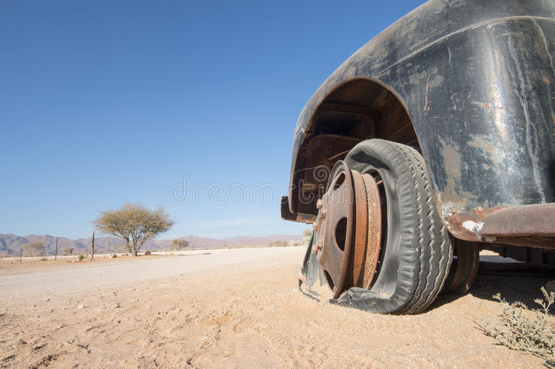 Desert car. Old, black car with a flat tire in the desert, concept for off-road sport or traveling and adventure, Namibia, Africa royalty free stock photo