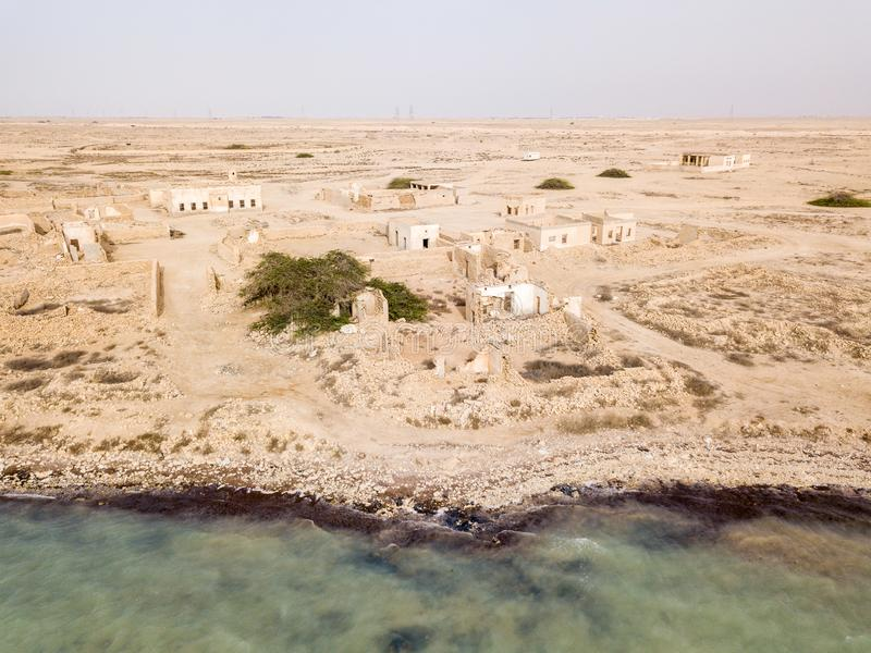 The desert at coast of Persian Gulf. Ruined abandoned traditional arab town Al Jumail, Qatar. Middle East. Ruined ancient old Arab pearling and fishing town Al stock photo