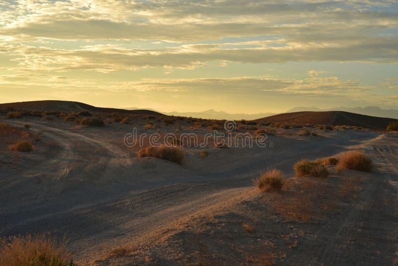 Desert dawn on dirt roads. Early morning light streaks color through the cloud filled sky over distant mountain range, closer hills, and sandy desert landscape stock photos