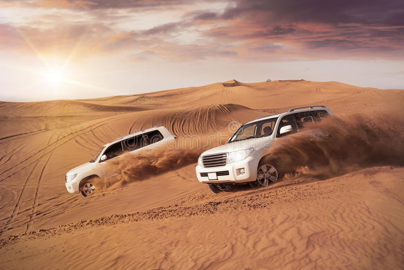 Desert Dune Bashing. Two 4x4 vehicles bashing side to side through the desert dunes in the evening sun stock images